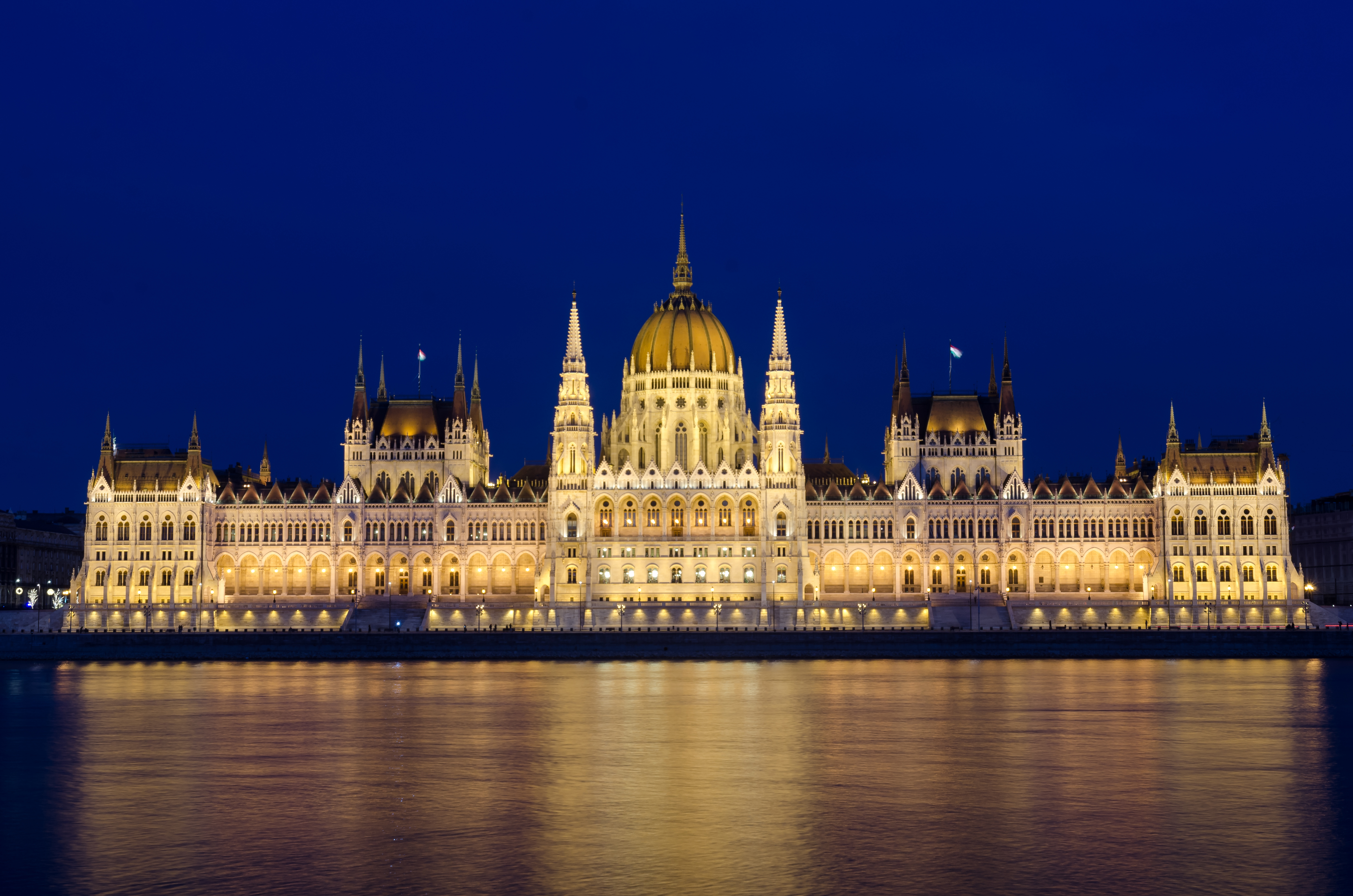 Illuminated Budapest hungarian Parliament at night reflected in the Danube river.